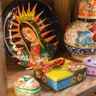 Glazed plates of Lady of Guadalupe and other cultural items on display as decorative crosses and traditional dresses line the walls of La Boutique International at Market Square.
