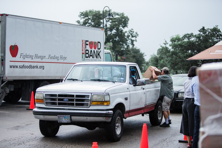 A volunteer loads a truck with a food box from the San Antonio food bank on June 11, 2019.