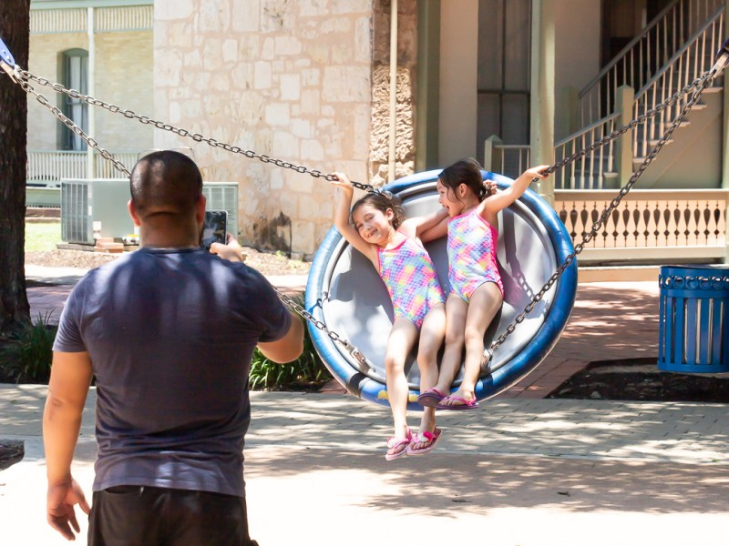 A father photographs his daughters as they swing at Hemisfair Park on June 18, 2019