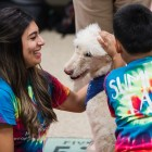 Cassandra Villarreal, a graduate student of Our Lady of the Lake University assists a young child petting a PAWS for Service dog on June 25, 2019.