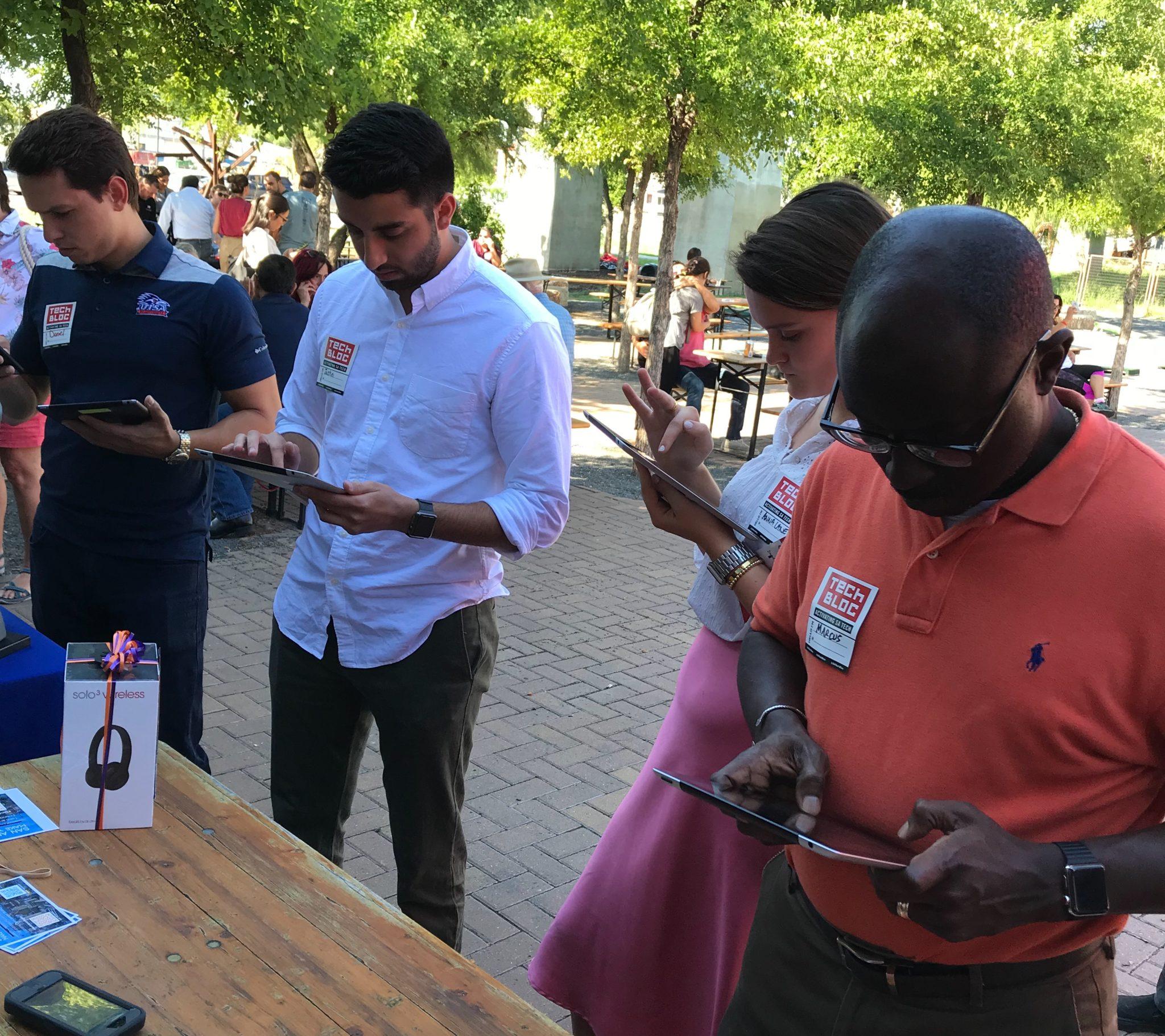 Tech Bloc event attendees take the San Antonio Regional Economic Development Strategy survey during a meetup.