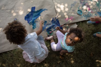 (From left) Rory, 3, and Reva, 18 months, paint on a sheet of paper.