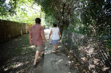 (left) David Schmidt and (right) Mimi Quintanilla walk down the green belt, which the neighborhood maintains.