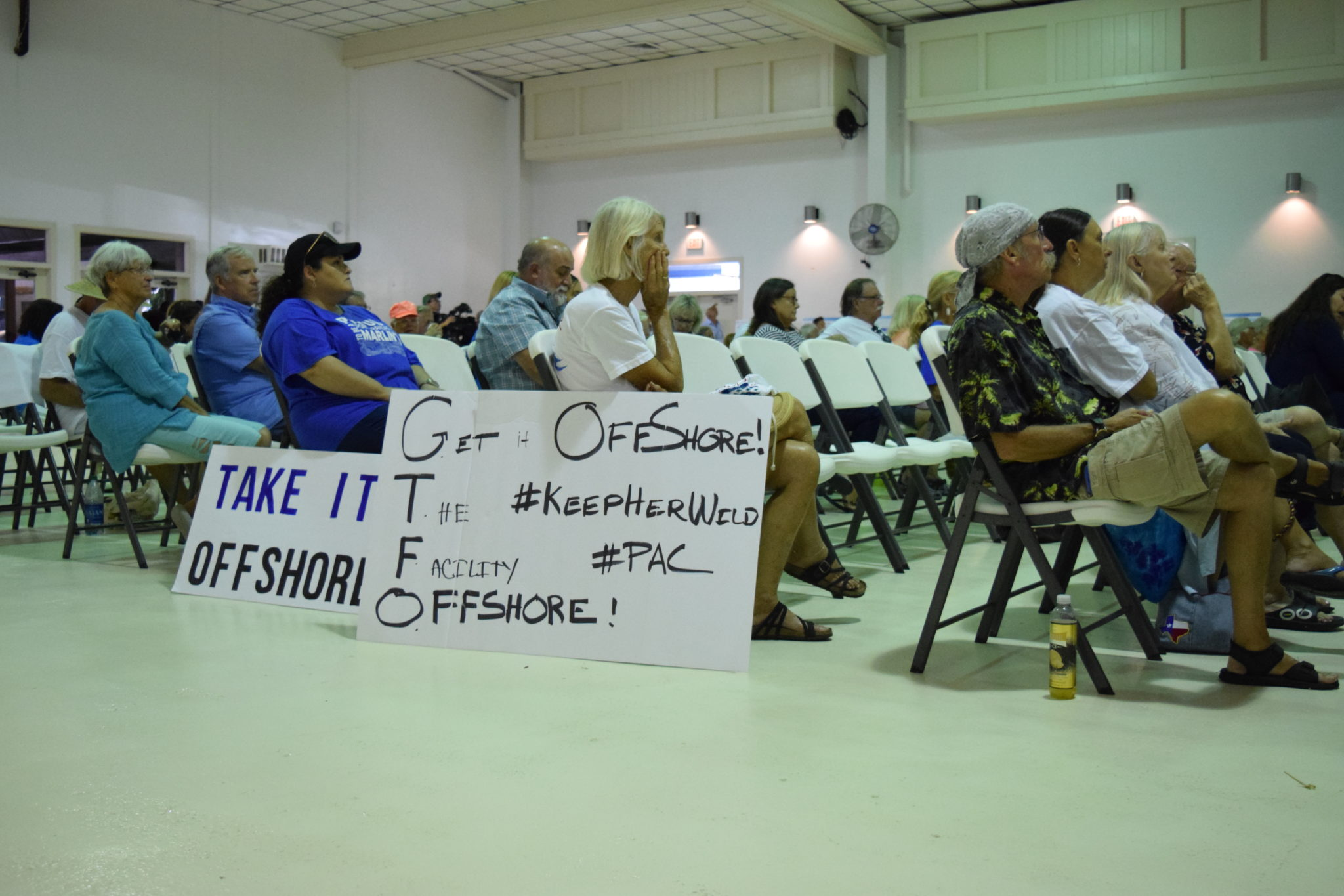 Attendees of a Port of Corpus Christi public meeting in Port Aransas hold signs calling for a proposed oil terminal to be built off-shore and not near the beach town.