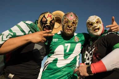 (From left) Frankie Garcia, Carlos Desrada, and Jorge Rivas wear lucha libre masks to support the Mexican National Soccer Team.