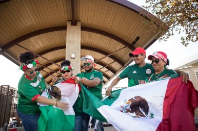 (From left) Blanca Rodriguez, Olga Montoya, Gustavo Gonzalez, Juan Garcia, and Marta Torres unfold their Mexican flags before the game.
