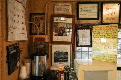 Signage, cards of gratitude, and awards are displayed on the walls of B&B Tamales.