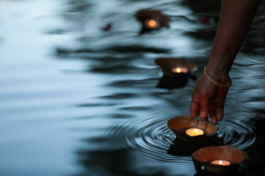 A diya (lamp) is placed into the San Antonio River during the ceremony.