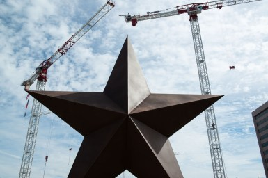 The Texas Facilities Commission's Capitol Complex construction project uses three cranes behind the Bullock Museum's star.