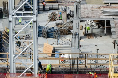 Construction workers erect a five-level parking garage that will be under the George H.W. Bush State Office Building.