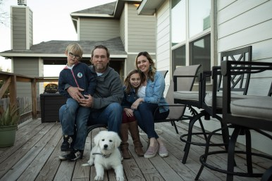 (From left) Oliver, 7, Kenny, Adelaide, 11, and Emilee Sargeant share a moment with their puppy Alpine on their back porch.