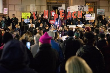 Hundreds gather with impeachment signs in front of the Federal Building and U.S. Courthouse.