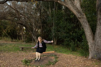 Mitzi Moore sits on the tree swing in the community garden.