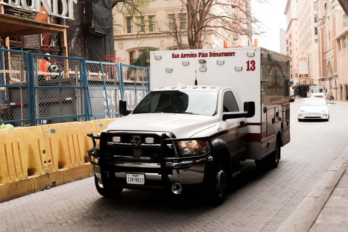 An ambulance drives South on Saint Mary's Street through downtown San Antonio.