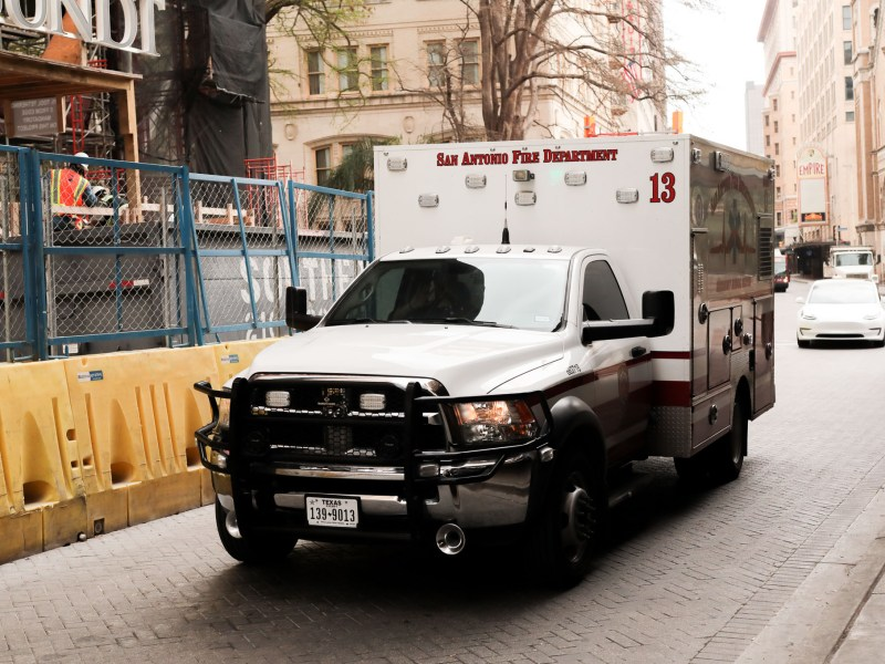 An ambulance drives South on Saint Mary's Street through downtown San Antonio.