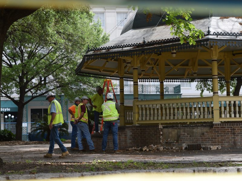 Construction workers cluster outside the bandstand at Alamo Plaza on Thursday, April 9, 2020.