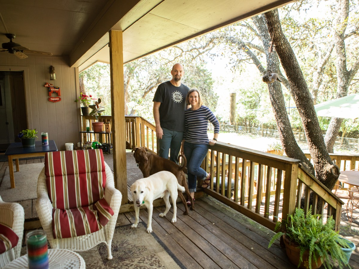 Julie Silvius Magadance, Steve Magadance, and their dogs Clay and Chuck stand on the deck in their backyard.
