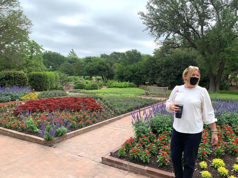 San Antonio Botanical Garden CEO Sabina Carr admires the flowers during a tour of the grounds on its 40th anniversary and first day open since the coronavirus pandemic reached San Antonio.
