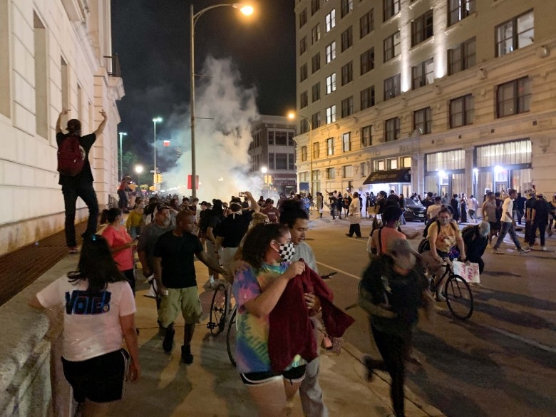 Protestors run as police begin using tear-gas to break up crowds that broke into and looted shops at Alamo Plaza.