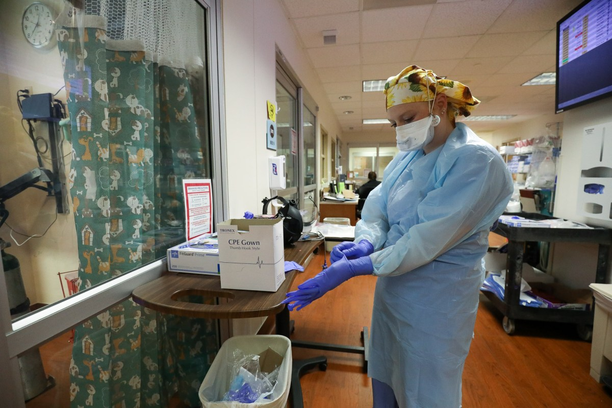 A nurse in the COVID-19 intensive care unit assembles layers of personal protective equipment and slips a second pair of examination gloves over her hands on June 19.