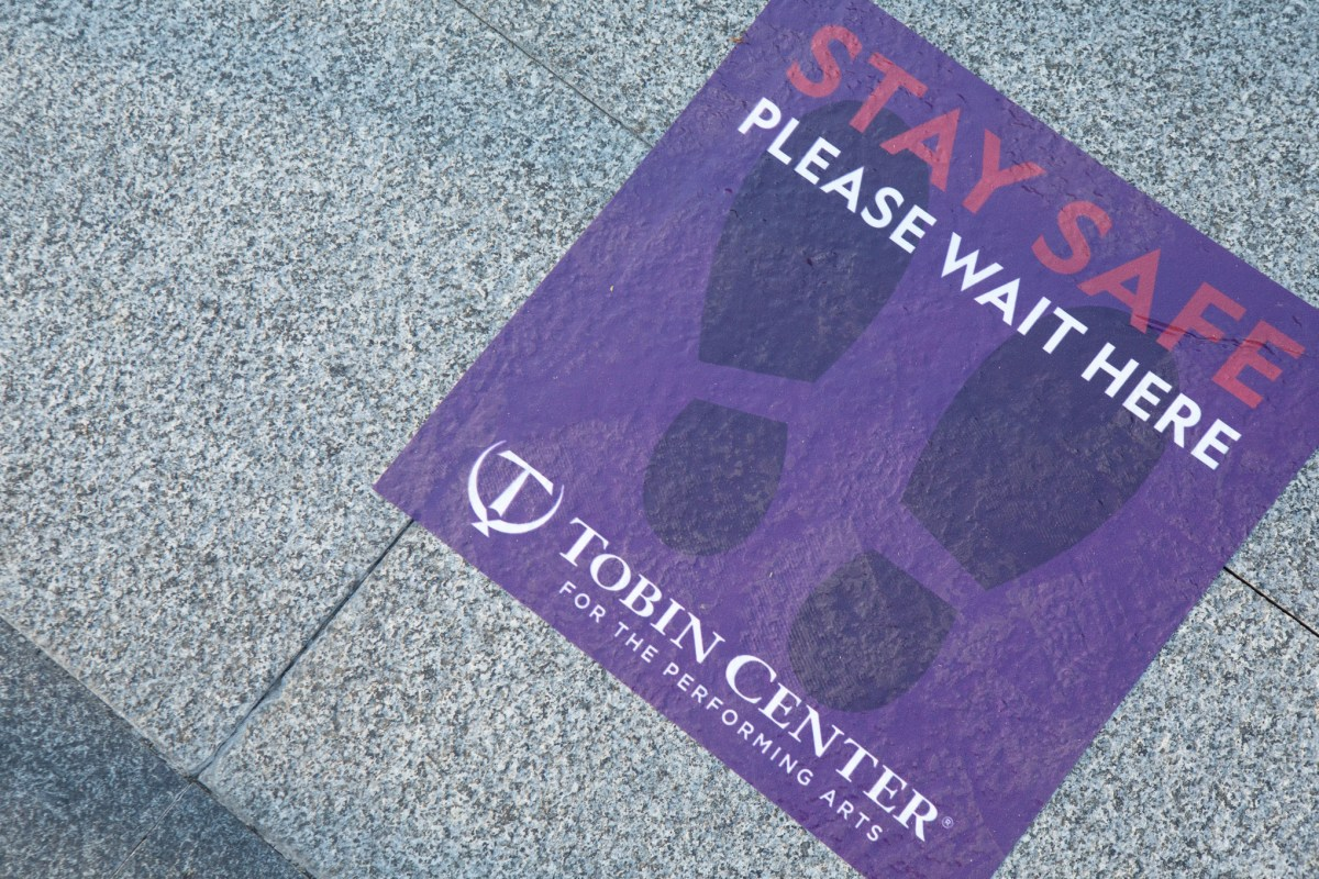 A sign promotes social distancing at Tobin Center for the Performing Arts.
