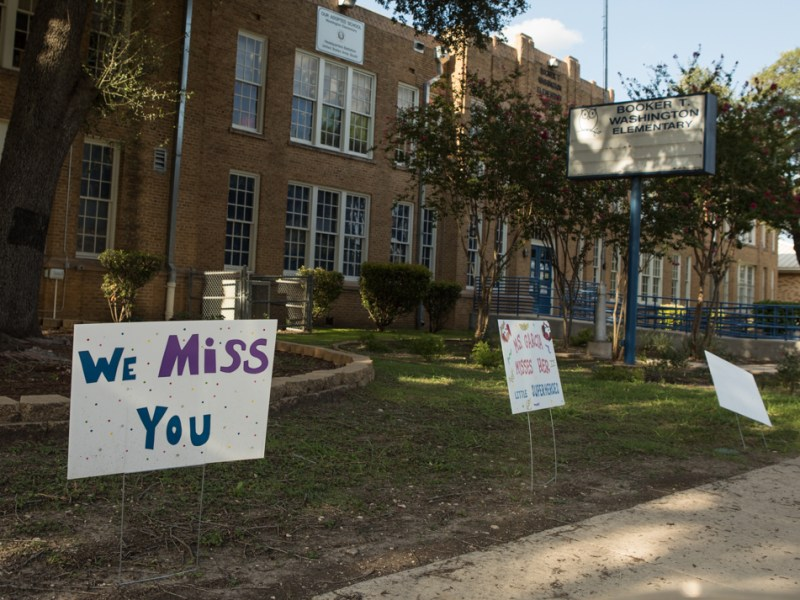 """A sign outside of Booker T. Washington Elementary School says, """"We miss you."""""""