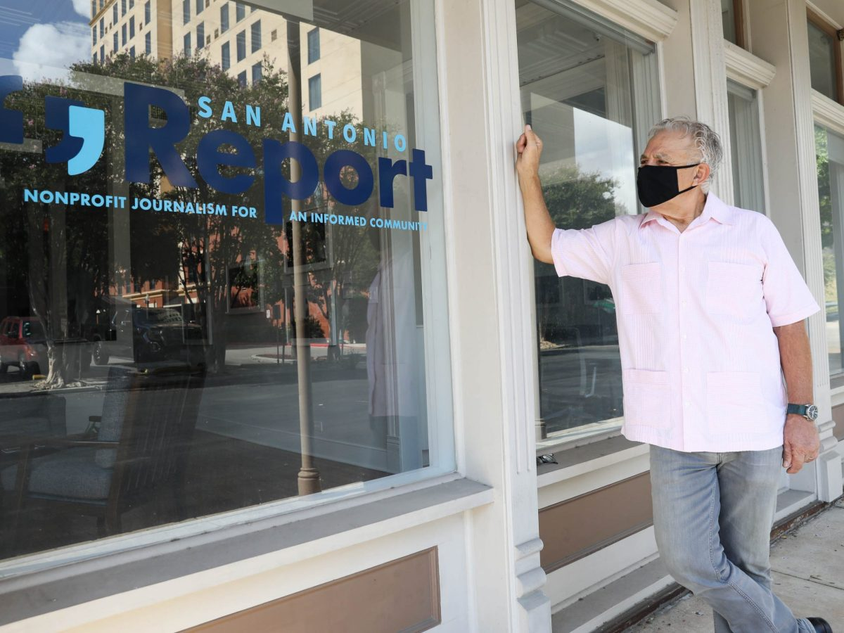 Editor Robert Rivard looks at a decal displayed on the window of the San Antonio Report's downtown office. The San Antonio Report was renamed last year.