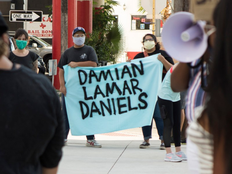 "Protesters hold a sign that says ""Damian Lamar Daniels"" at a Black Lives Matter protest in front of the Bexar County Sheriff's Office and Detention Center on Wednesday."