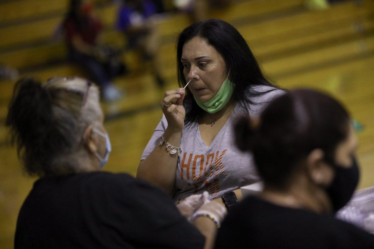 Nanette Ortega, a science teacher at Somerset High School self-administers a coronavirus test in the school gymnasium.
