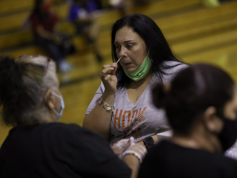 Nanette Ortega, a science teacher at Somerset High School self-administers a coronavirus test in the school gymnasium.