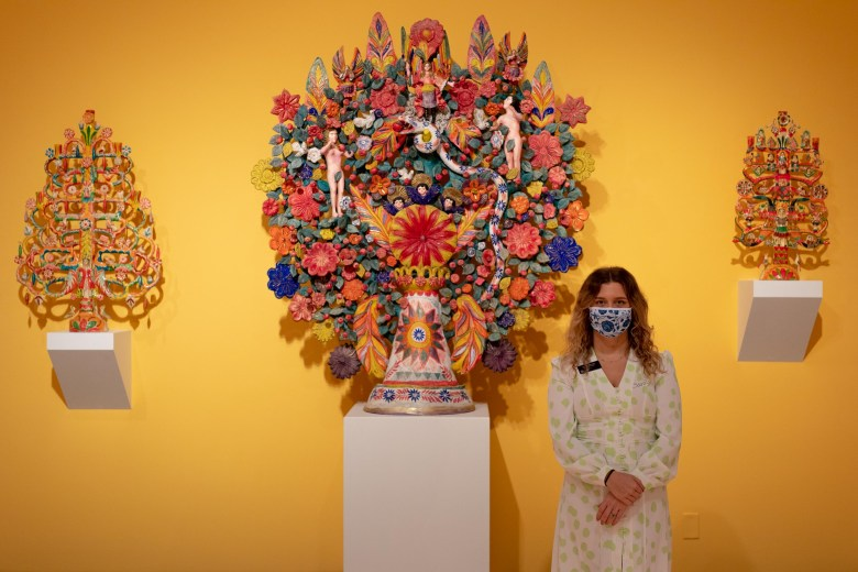 Lucia Abramovich, curator of Latin American art at the San Antonio Museum of Art, stands in front of large trees of life featured in the Latin American Popular Art gallery.