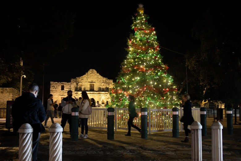 Downtown visitors admire a large Christmas tree donated by H-E-B at Alamo Plaza on Friday evening.