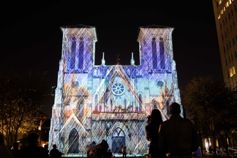 Downtown visitors watch The Saga art installation projected onto San Fernando Cathedral on Friday night.