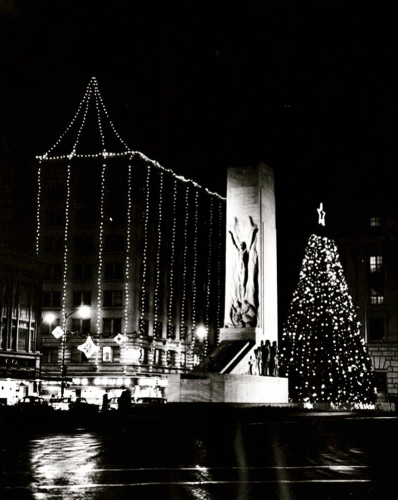 Holiday lights with the Gibbs Building and the Rotary Club Christmas Tree in Alamo Plaza in the 1950s.