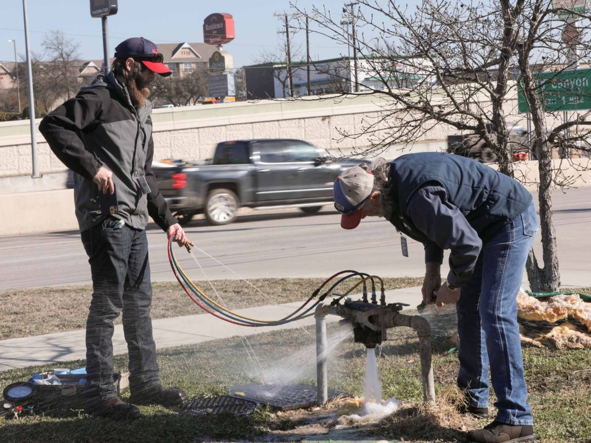 Aaron and Jerry Mulder of Mr. Rooter Plumbing San Antonio work to repair a backflow preventer outside of the Hoppy Monk restaurant on the far North Side.