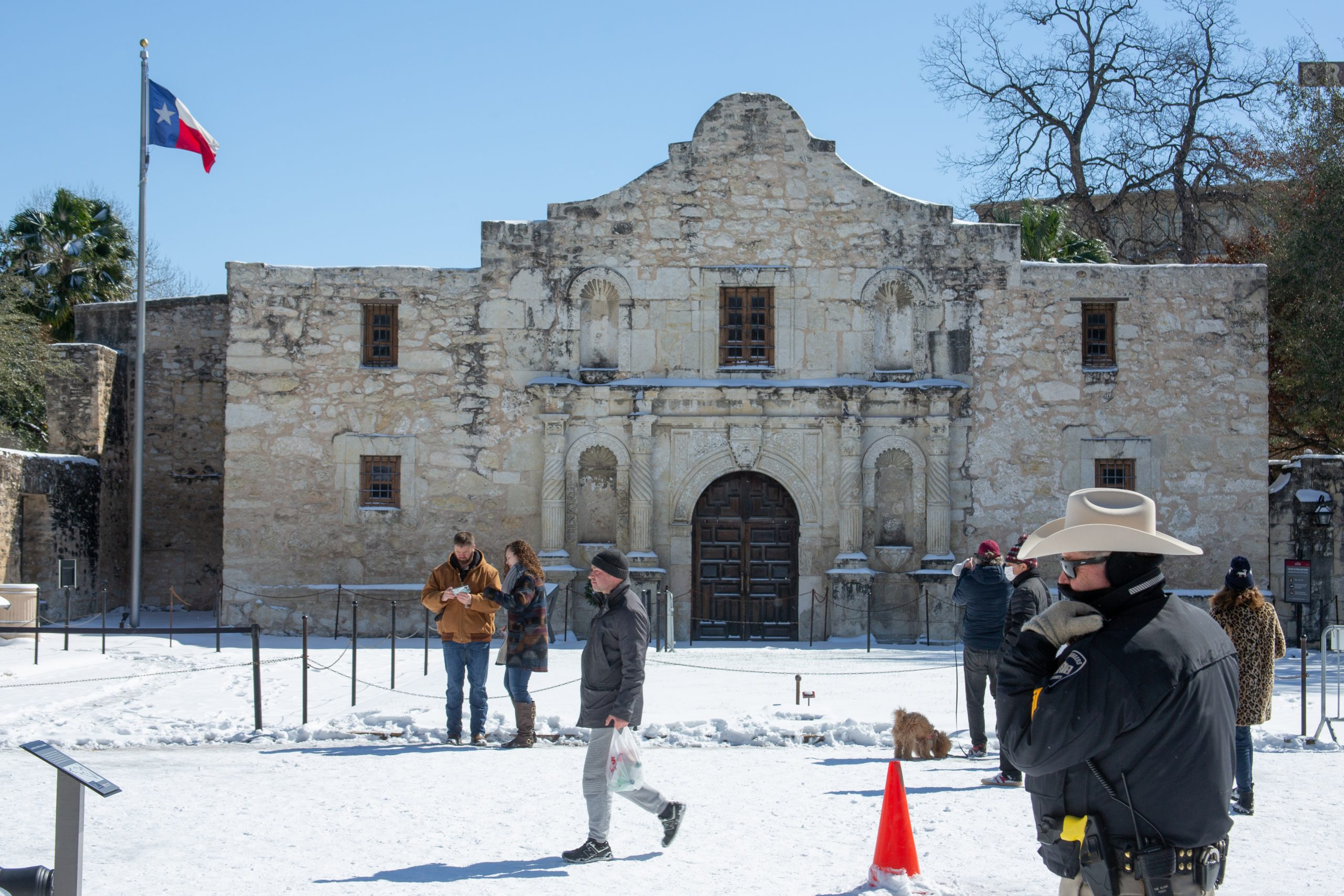 Visitors at Alamo Plaza take photographs in front of the snowy scene at the historic site.