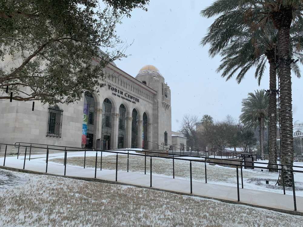 Snow falls at the Tobin Center for the Performing Arts on Thursday.