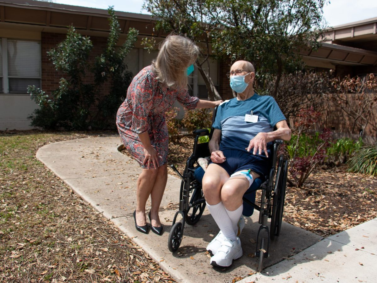 Sandy Cilone chats with her 95-year-old father, Eldon Webb, outside of Morningside Manor, an assisted living facility that limits guests during the COVID-19 pandemic. Tuesday, March 16, 2021.