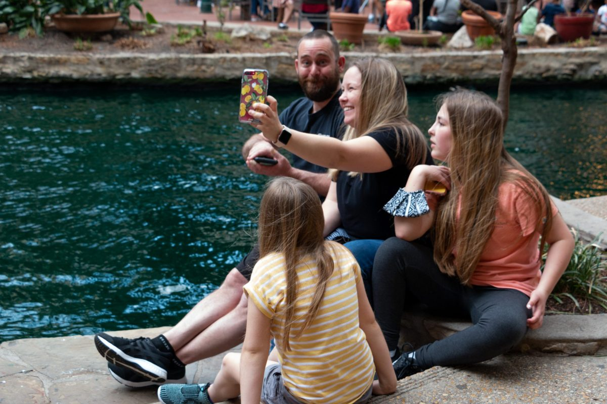 A family takes a selfie while sitting along the San Antonio River Walk during spring break.