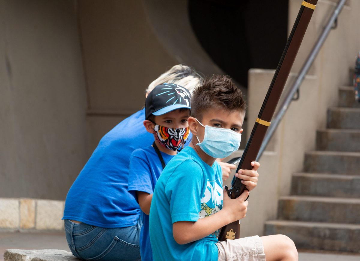 Two boys play with souvenirs while sitting along the San Antonio River Walk during spring break.