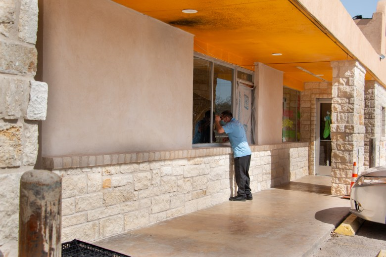 A man peers through the window of a business to see if it is open in the Mac Arthur Plaza Shopping Center on Nacogdoches Road. Many businesses in this shopping center have closed their doors due to the COVID-19 pandemic. Monday, March 15, 2021.