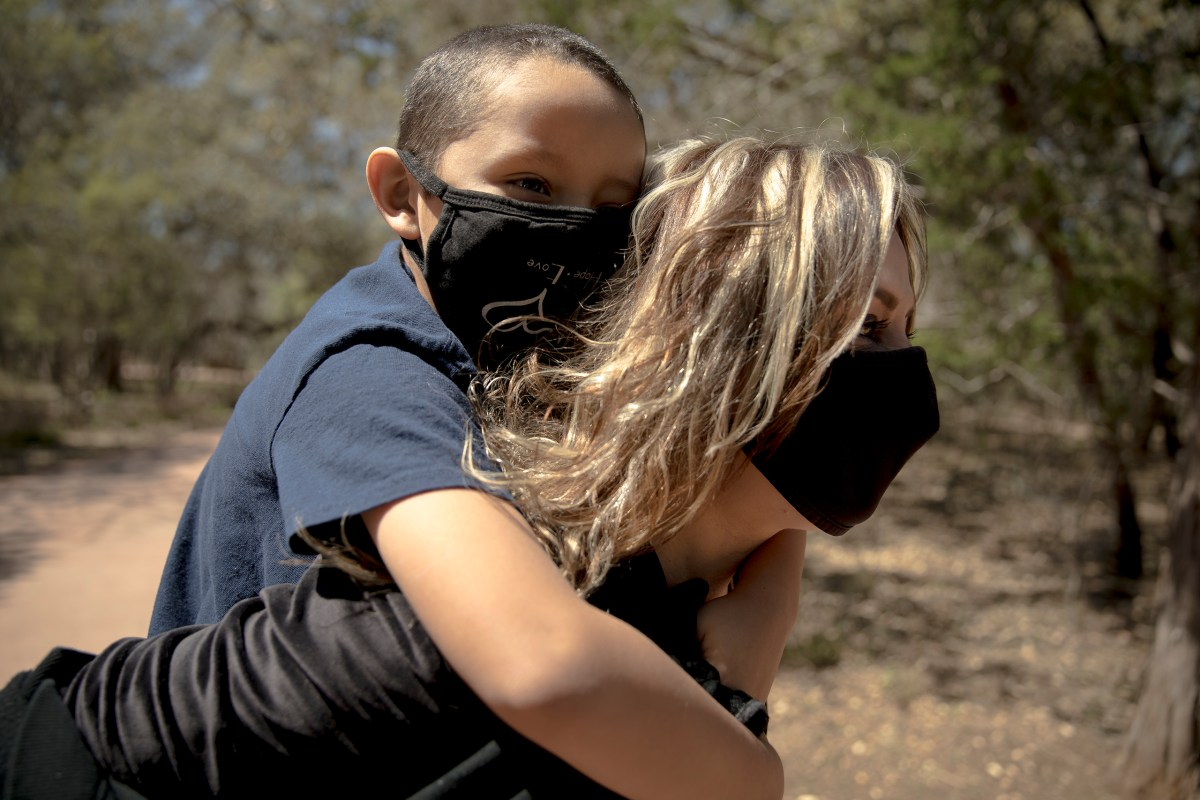 Iris Nuno gives her 6-year-old son, Jared, a piggyback ride along the Salado Creek Greenway on Saturday in San Antonio.