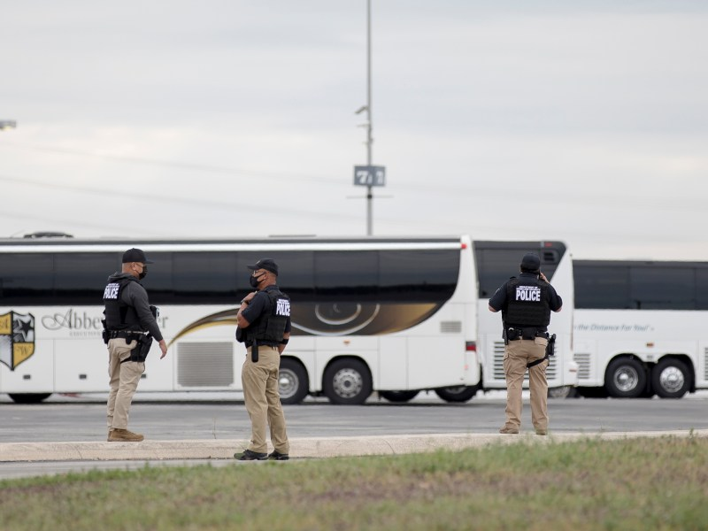 Department of Homeland Security police officers stand guard near buses used to transport migrant children from the border to the Freeman Coliseum.