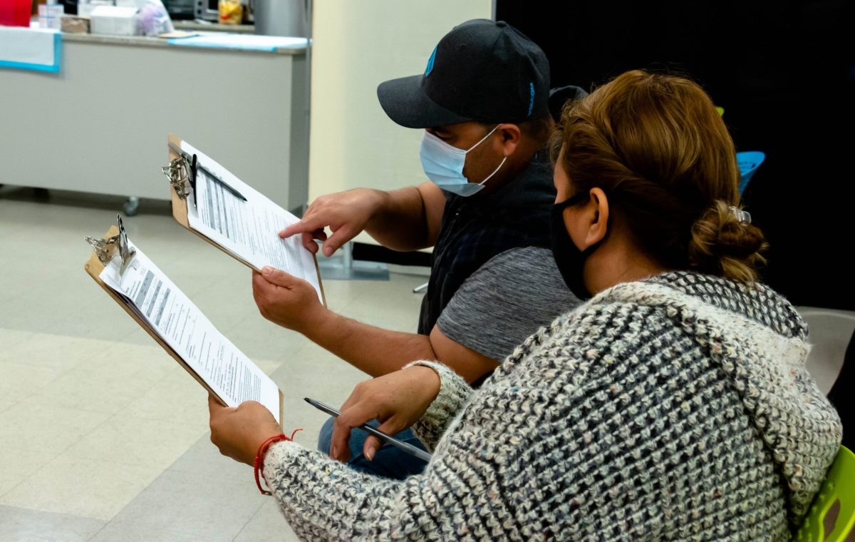 Lucia and Jose Esquivel fill out paperwork to get her COVID-19 vaccine at the Gonzaba Medical Group vaccine clinic.