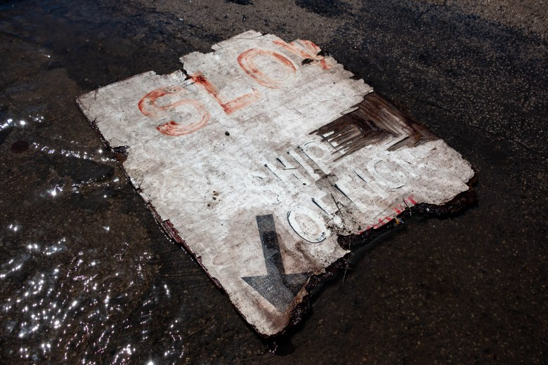 """A fragment of a sign that reads """"Slow"""" """"Ship"""" and """"Office"""" floats in a puddle of water created by the runoff from the gallons of water firefighters continued to spray onto the old Lone Star Brewery building Sunday morning."""