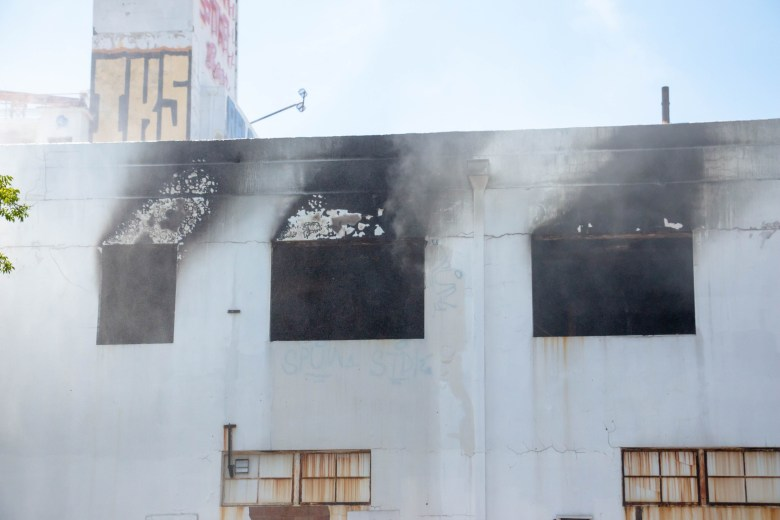Water vapor billows out of charred windows on an upper floor of the abandoned Lone Star Brewery building. The 32-acre property has been vacant for almost 30 years.