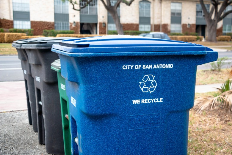 The recycling bin sits next to other waste bins outside of a home on W Mistletoe Avenue.