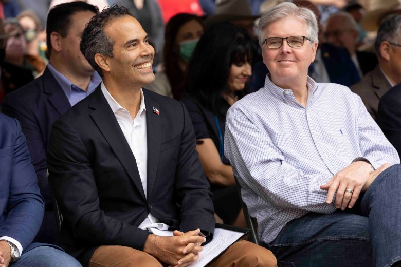 Texas Land Commissioner George P. Bush, left, and Lt. Gov. Dan Patrick smile as they sit next to each other during a Alamo ceremony unveiling an 18-pounder Swiss cannon, a replica of one that was used during the historic battle.
