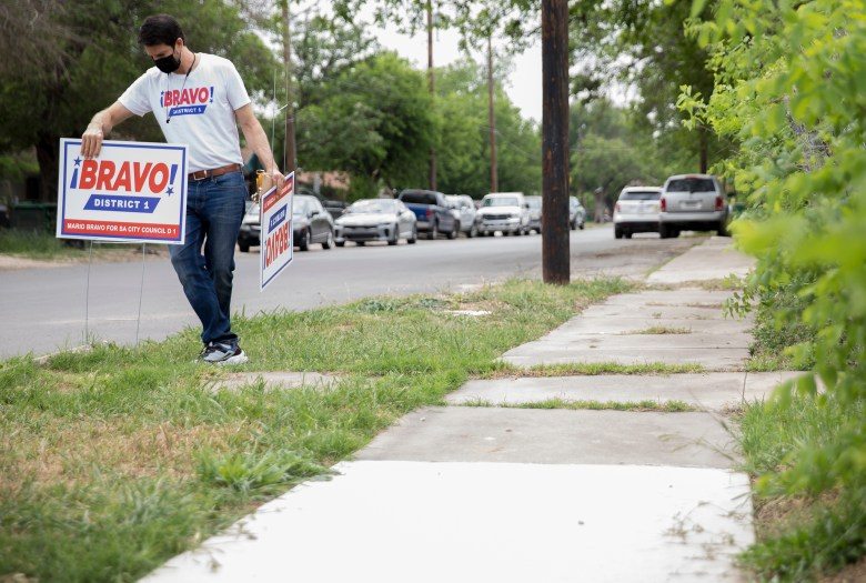 District 1 City Council candidate Mario Bravo places a campaign sign along a supporter's boulevard on Tuesday.