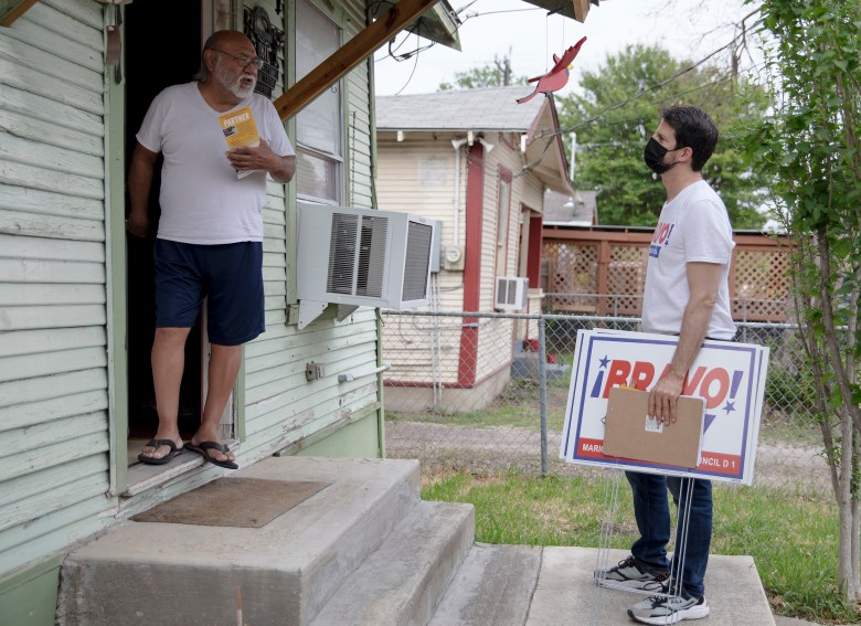 District 1 City Council candidate Mario Bravo listens to the concerns of Roy Sandoval about his neighborhood on Tuesday.
